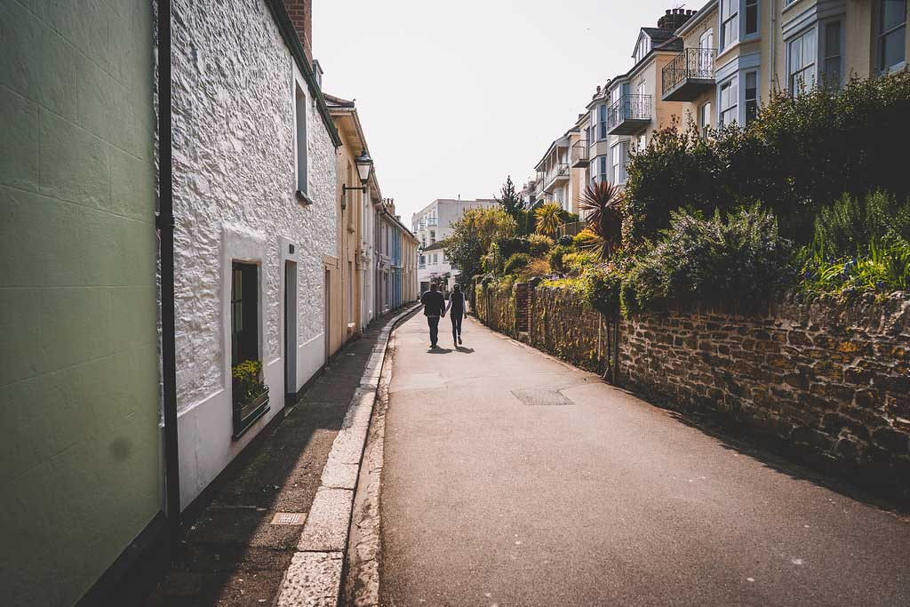 Couple-walking-down-quaint-street-in-cornwall