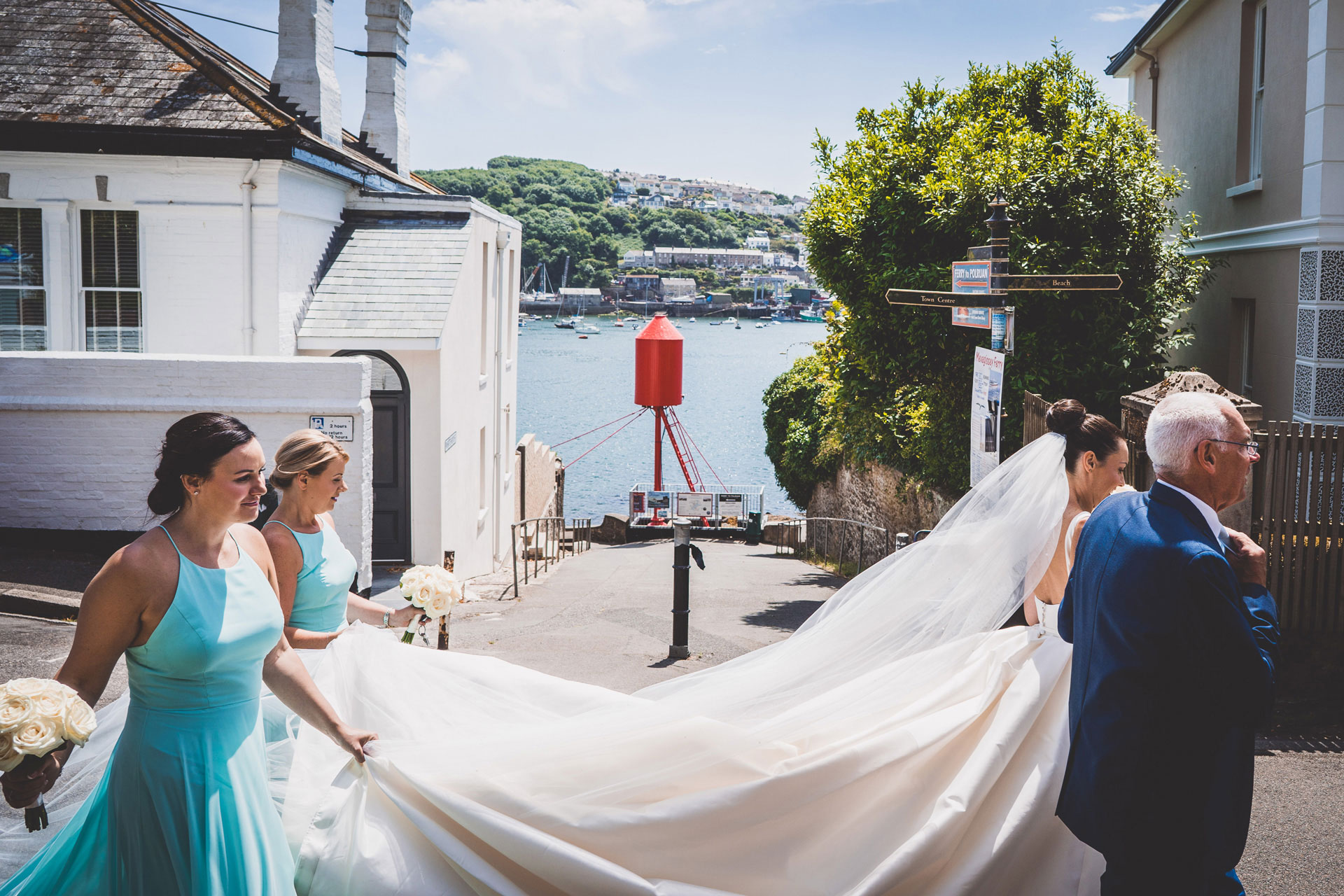 bride-and-her-father-walking-down-street-in-cornwall-on-the-wedding-day-bridesmaids-in-light-blue